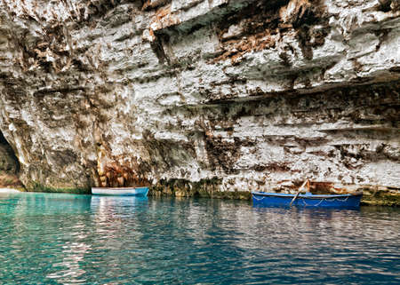 two wooden boats in old cave with clear blue water photo