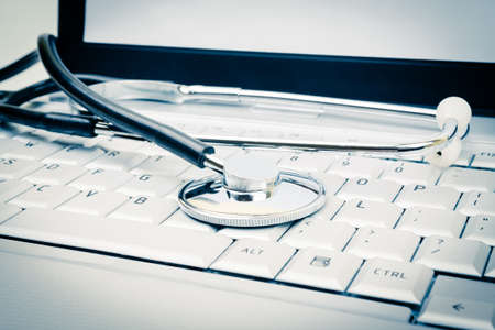 stethoscope on laptop keyboard, blue sepia tinted