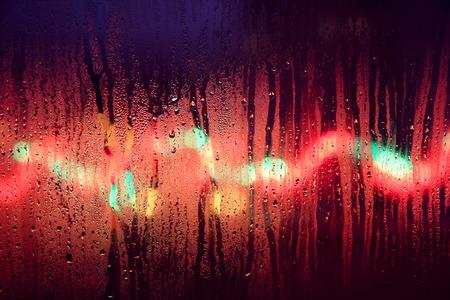 horisontal: Blurry colorful Christmas lights behind a rainy window