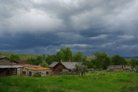 Old houses and dark cloud in Bannack, Montana Stock Photo