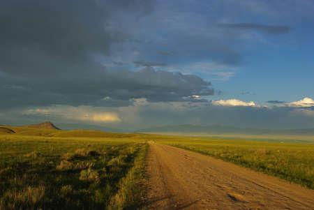 dillon: Gravel road, grasslands and mountains near Dillon, Montana Stock Photo