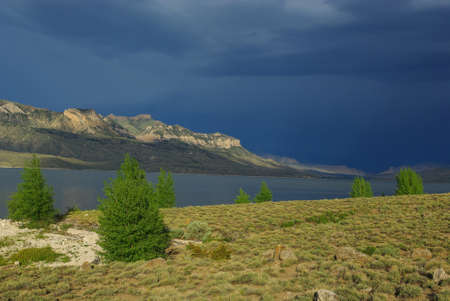cody: Sun and dark cloud on Buffalo Bill Reservoir, prime grizzly habitat near Cody, Wyoming Stock Photo