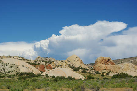 Colored rocks under blue sky and big clouds in Dinosaur National Monument near Vernal, Utah Stock Photo