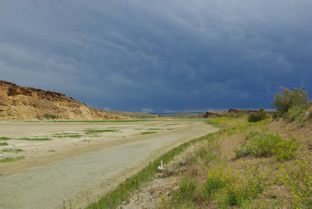 Dry river bed, sun and clouds, Montana photo