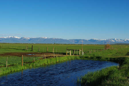 vast: Blue water, green plains and high Rockies, Colorado Stock Photo