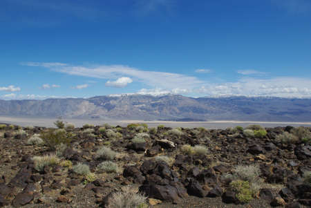 near death: Black rocks above wide valley and high mountains near Death Valley, California