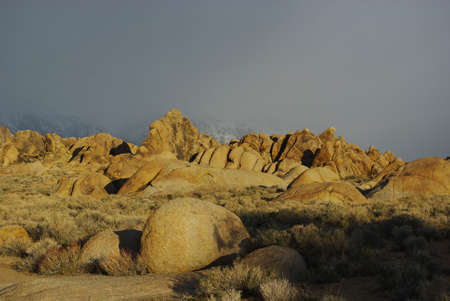 Sun on rocks and fog, Alabama Hills with snowy Sierra Nevada, California photo