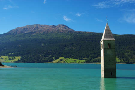Tower of sunken church in green Lake Resia with Elferspitze, Italy