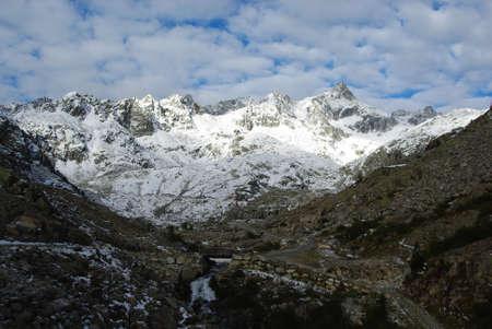 High mountain trail with small bridge and waterfall near Cima Presanella, Italy