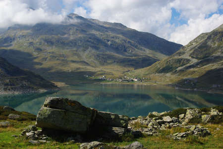 Lake Montespluga with village of Montespluga and Alps, Italy