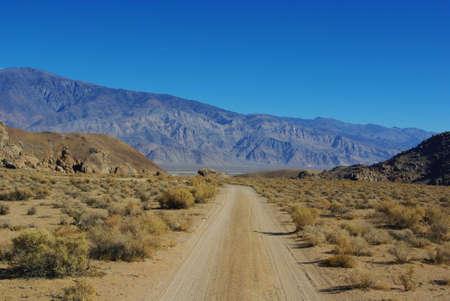 Sandy road through rocks to high mountains Stock Photo