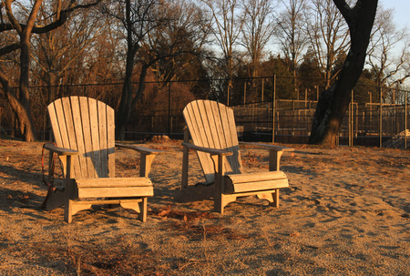 wooden beach chairs at sunset