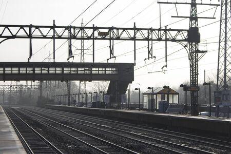 silhouetted footbridge over tracks at suburban train station