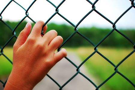 Hands on a prison fence with nature behind