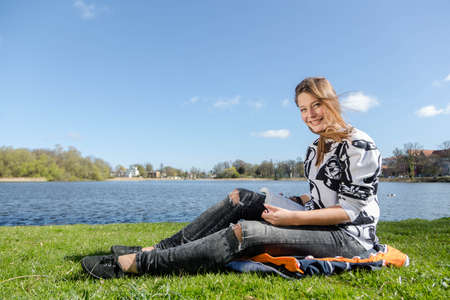 studied: A woman reads a book in a park during nice weather and laughs into the camera Stock Photo