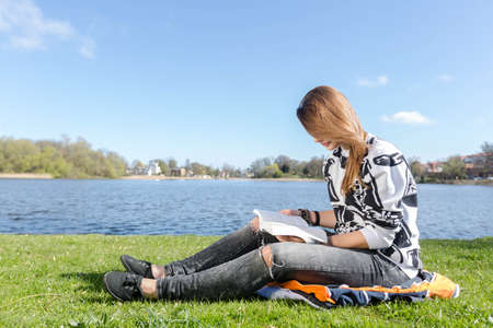 studied: Girl reading and skimming through a book during nice weather in a park Stock Photo