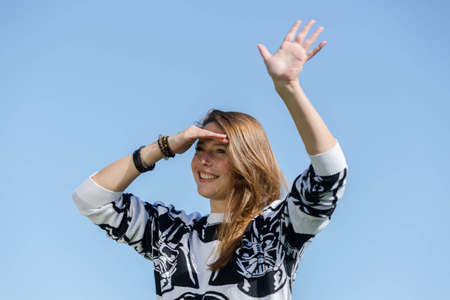 recognizes: Laughing young woman recognizes her friends and waves them with one hand Stock Photo