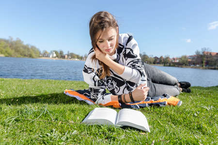 studied: Young woman reading a book and runs his hand through her hair