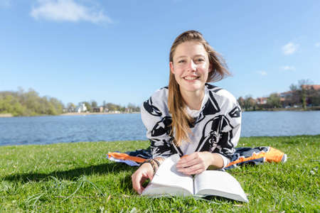 studied: A young woman lies at a lake and laughs into the camera during nice weather Stock Photo