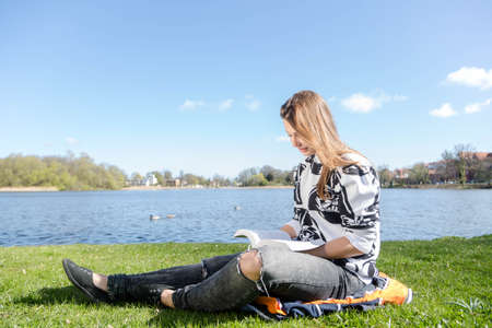 studied: A woman reads a book in a park during nice weather Stock Photo