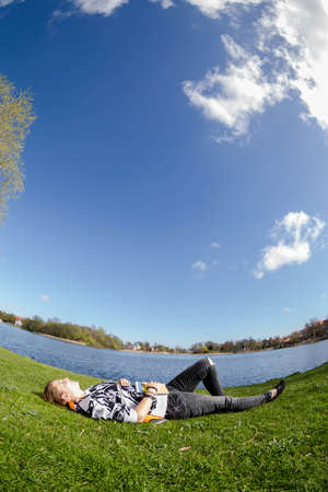 naptime: Girl relaxing on a meadow at a lake during nice weather Stock Photo