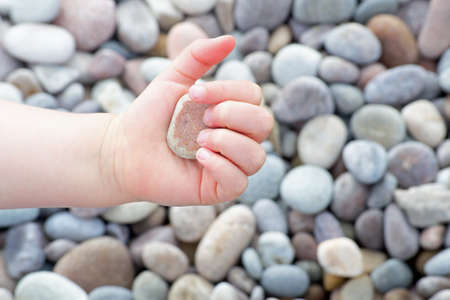 clutches: Baby hand clutches a pebble Stock Photo