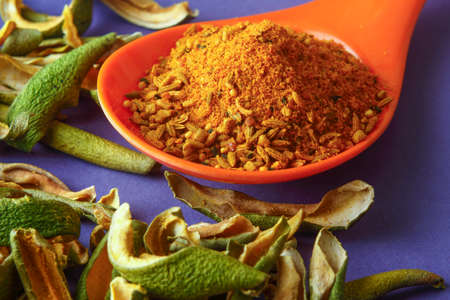 close up of indian achar masala with dry mango  slice inm a spoon