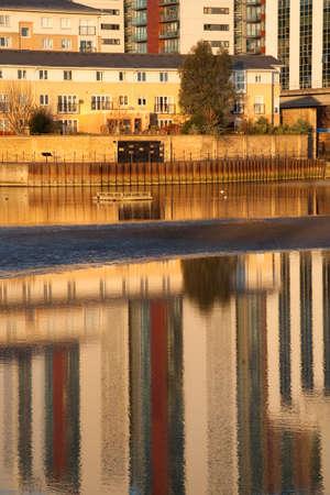 City apartment building and office reflections. Warm evening sunlight and water reflections.