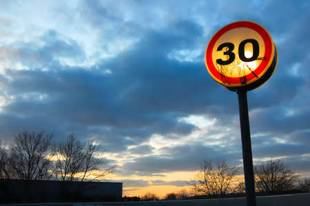Glowing speed restriction sign set against dramatic evening cloudy sky.