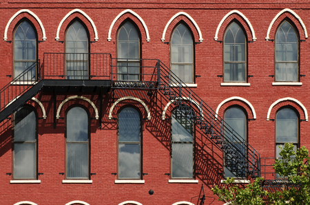 red brick repetition: Windows with white trim and a fire escape in a red brick building