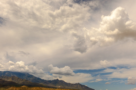 Mountain in lower third of frame with clouds and blue sky at top.