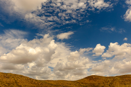 horizontals: Mountain in lower third of frame with clouds and blue sky at top.