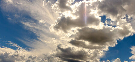 pano: Feathery and solid clouds contrast in a heavenly sky and feature a rainbow sundog, pano. Stock Photo