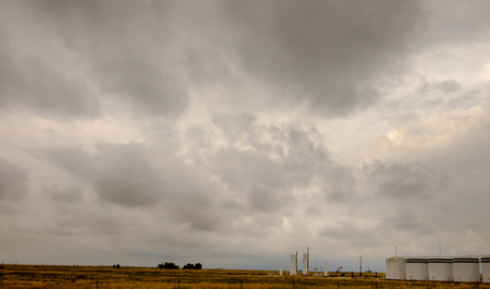 horizontals: Rural landscape of gas storage tanks, pumps, and cloudy skies