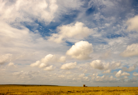 Rural landscape of gas storage tank and cloudy skies photo