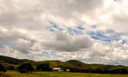 horizontals: Farm buildings nestled in green mountains under storm clouds, southeastern New Mexico