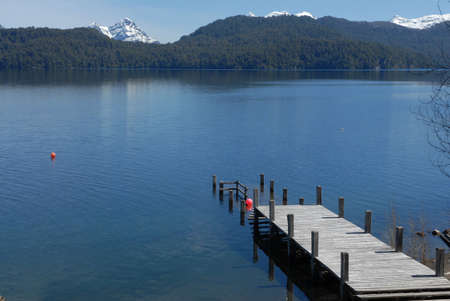 Wood pier, lake and mountains in Argentina photo