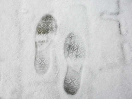 Two foot steps on white snow photo