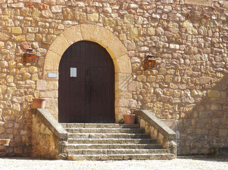 Medieval castle entrance with wooden door and steps in a bright day photo