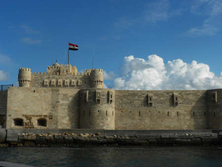 alexandria: Lateral view of Alexandria lighthouse with cloudy blue sky in Egypt Editorial