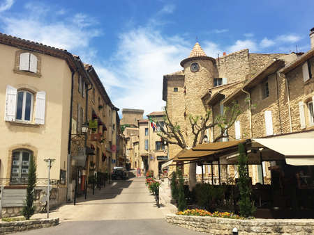 Perspective view of old houses in small french town with blue sky and clouds