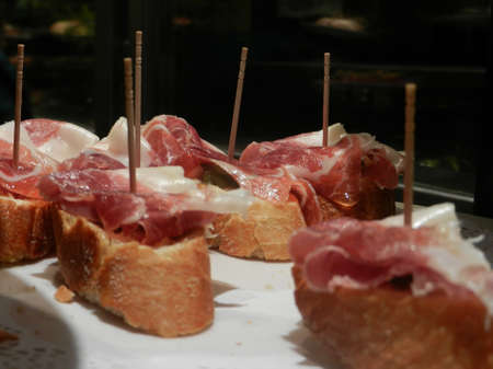 closeup of traditional spanish pinxtos of bellota ham on white bread