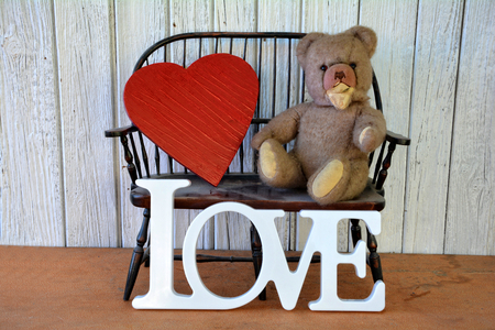 br: Age Teddy Br on bench with heart and lettering Love Stock Photo