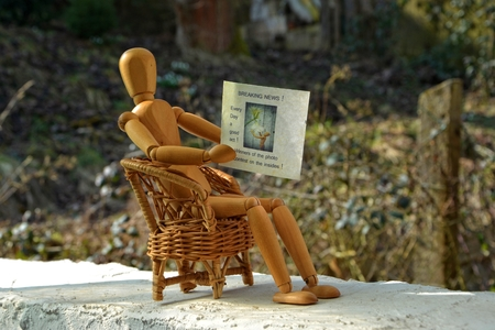 wooden figure: Wooden figure sitting on patio chair and reading newspaper