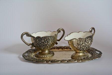 vecchio zuccheriera d'argento e crema sul vassoio d'argento e su uno sfondo bianco