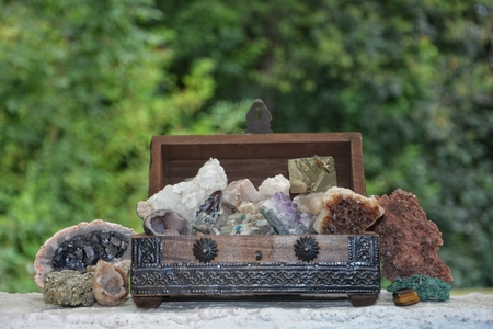 oxides: many minerals quartz and crystal stones in wooden box against green nature background