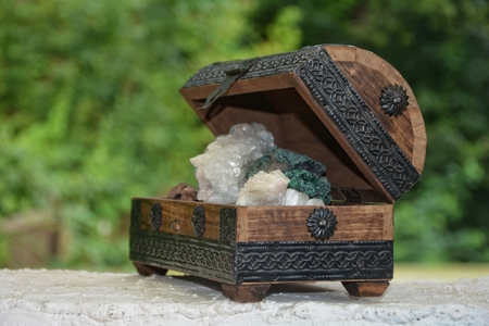many minerals quartz and crystal stones in wooden box against green nature background
