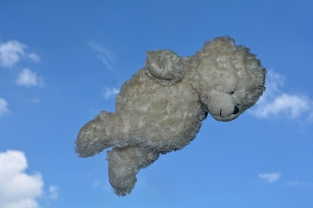 Teddy bear flies in the air with blue sky with clouds Stock Photo