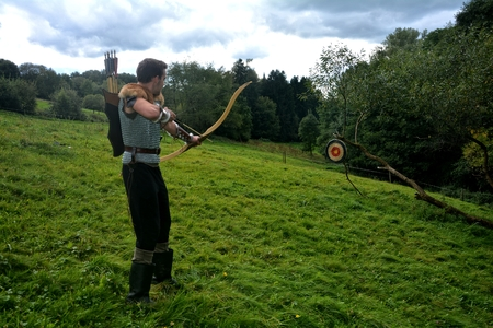 Young medieval archer of the side, aims with arrow and curve at straw disc in green nature Stock Photo