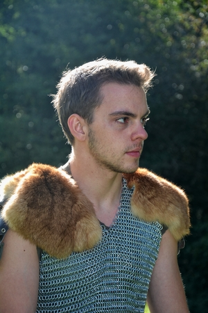 Young medieval, black-hairy man with chain shirt and fur in shoulders sits in the sunlight and looks aside Stock Photo